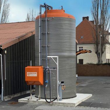 Vollständig aufgestellter Solelagertank aus GFK neben einem Firmengebäude
